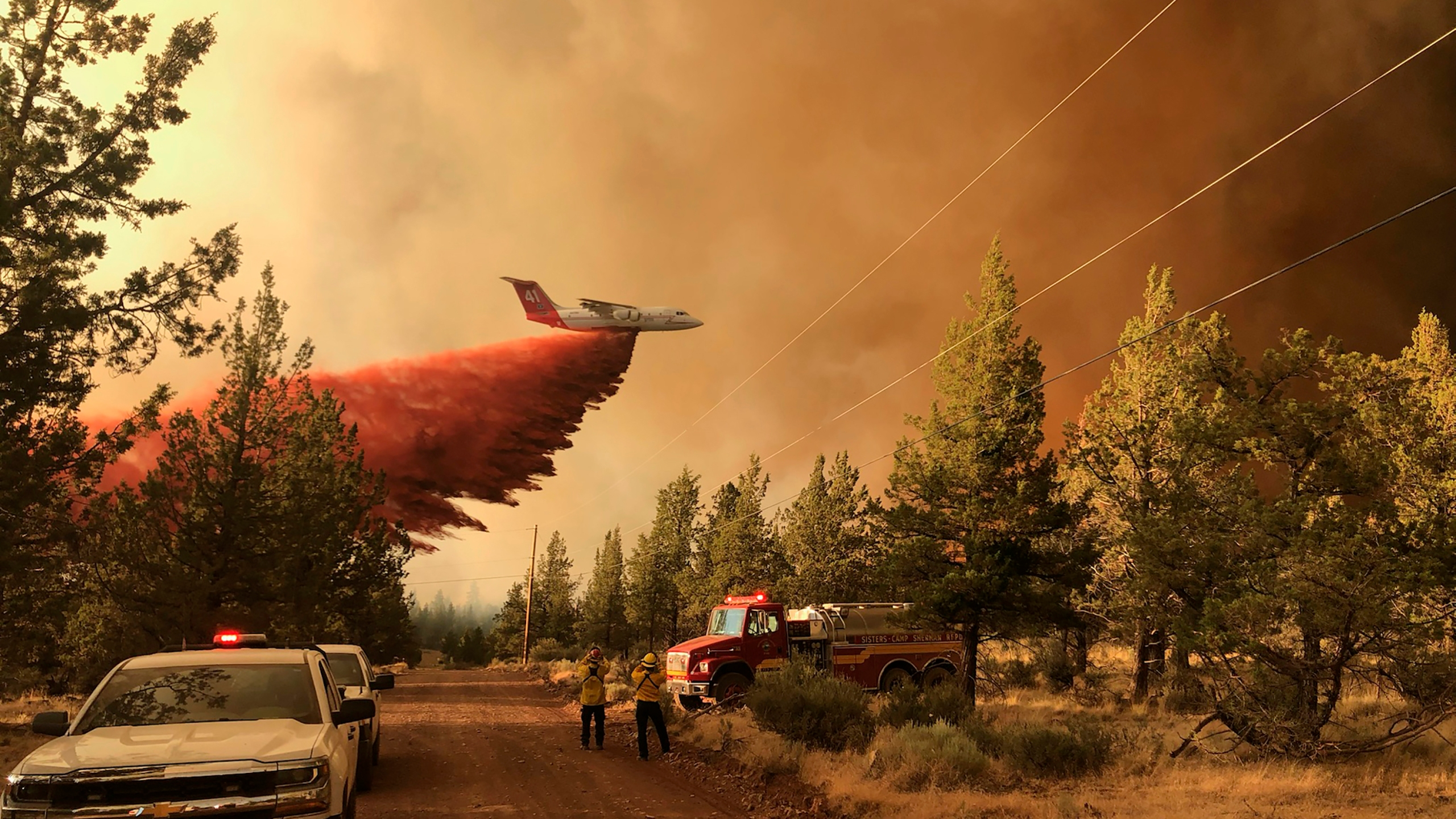 This photo provided by the Oregon Department of Forestry shows a firefighting tanker making a retardant drop over the Grandview Fire near Sisters, Ore., Sunday, July 11, 2021. (Oregon Department of Forestry via AP)